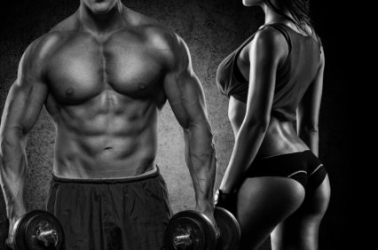 Fitness couple - woman and man with dumbbells in gym